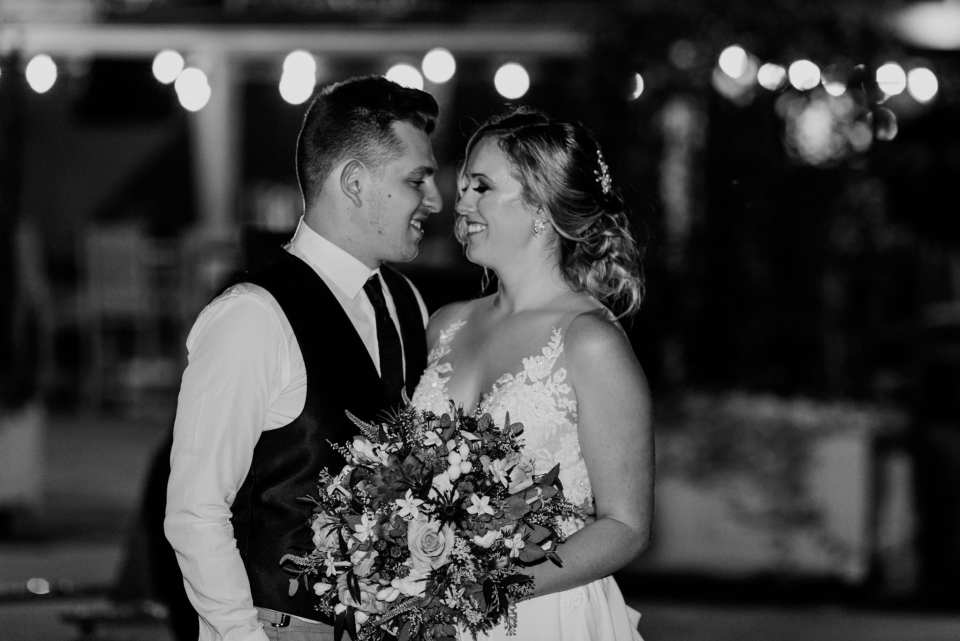 Black and white candid of the bride and groom outside at night, smiling at one another in these Blue Mountain Resort Wedding photos