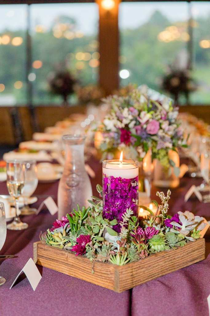 Wedding detail photo of a long rectangular table with short wildflower and green floral arrangements in small glass vases, surrounded by other lower wildflower arrangements by Ross Plants and Flowers