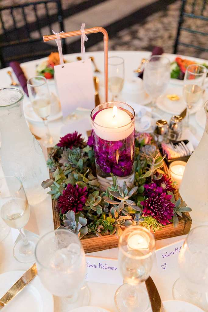 Wedding detail photo of floating candle and low wildflower arrangement by Ross Plants and Flowers