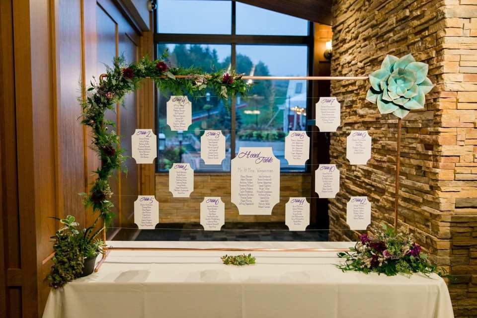 Unique seating chart display on copper pipe rack decorated with greens, wildflowers and succulents