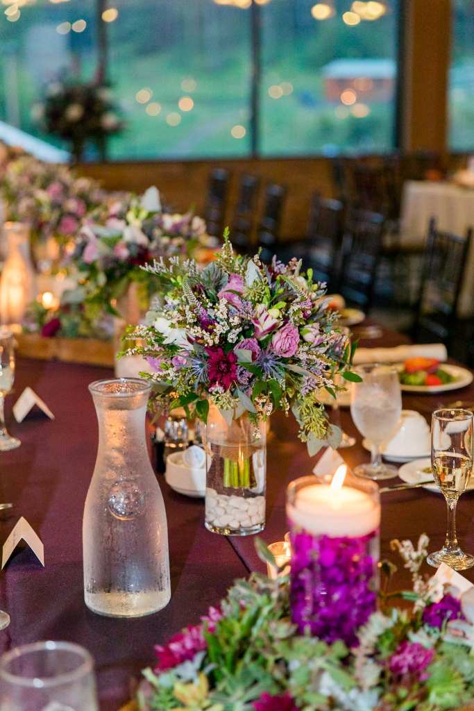 Wedding detail photo of a long rectangular table with short wildflower and green floral arrangements in small glass vases, surrounded by other lower wildflower arrangements by Ross Plants and Flowers in these Blue Mountain Resort Wedding photos
