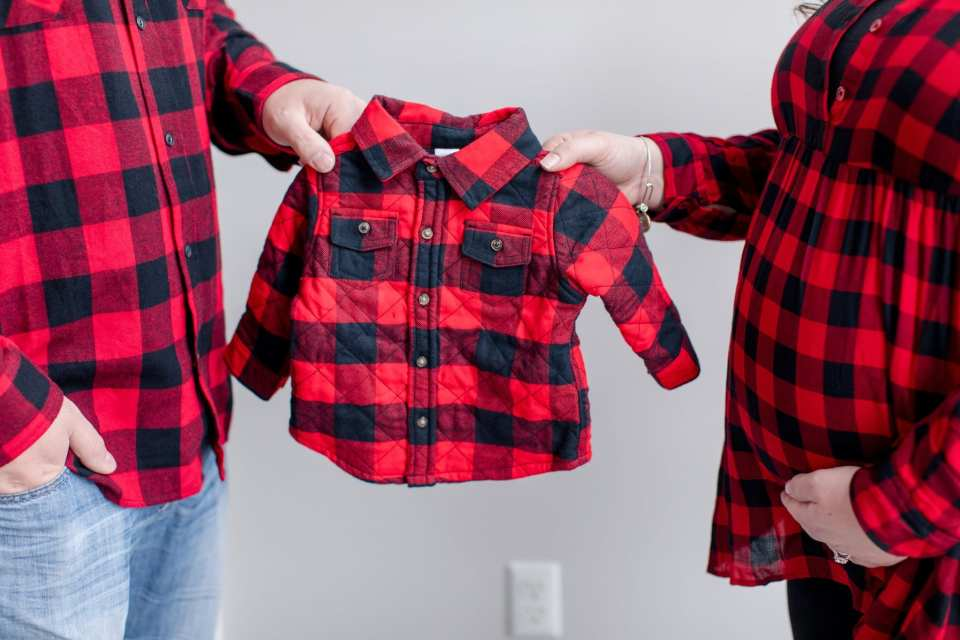 3/4 shot of parents to be in red flannel holding a coordinating red flannel shirt for their bundle of joy on the way