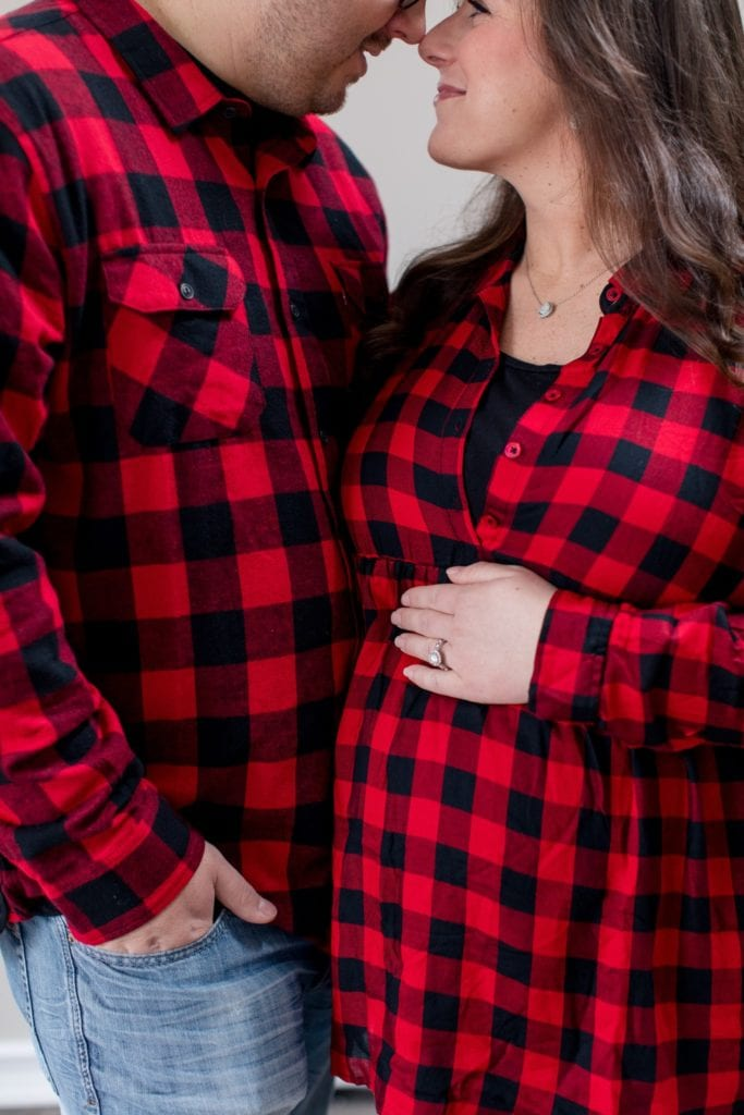 Mom and Dad to be, nose to nose, in coordinating red flannel tops