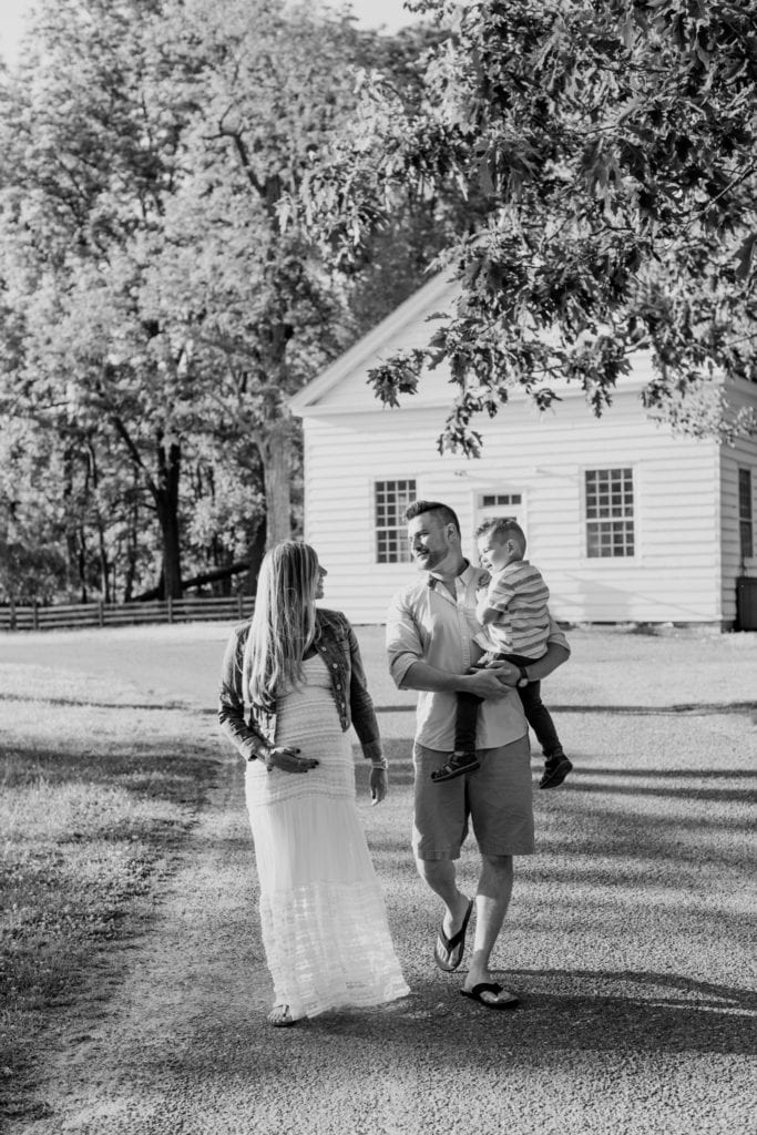 Black and white photo of Mom and Dad smiling and talking while Dad carries son on a path through a park