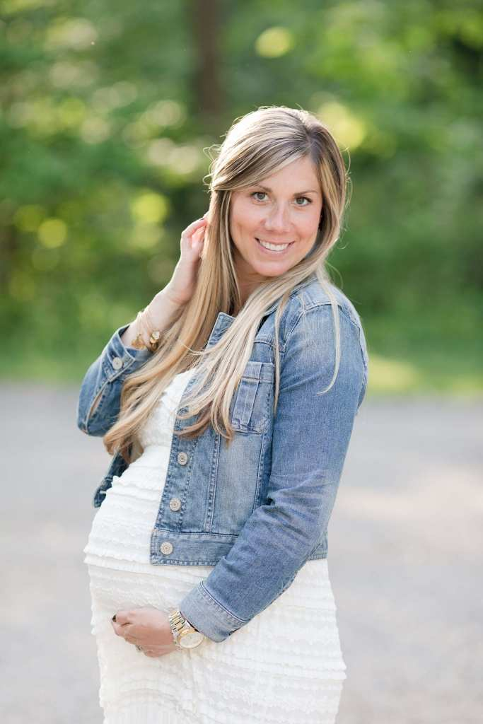 Portrait of pregnant Mom holding her belly, smiling at the camera