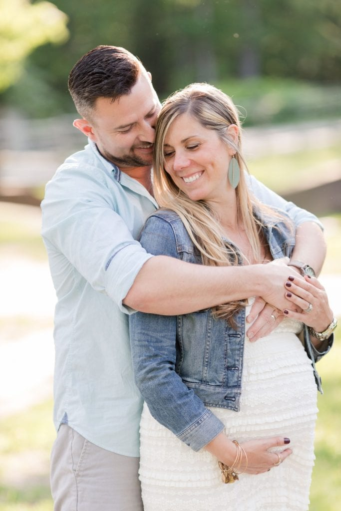 """Modified """"Prom pose"""" of husband standing behind his pregnant wife, his arms wrapped around her, while nuzzling her temple; she is smiling looking down, one hand supporting her pregnant belly. Maternity photos in NJ"""