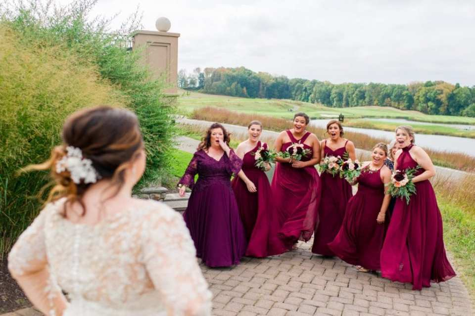 Candid of the bridal party in dark red, or wine, colored gowns by Azazie seeing the bride for the first time