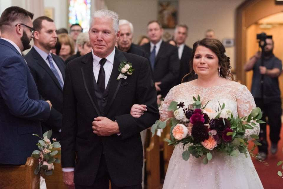 The bride being walked down the aisle by her father