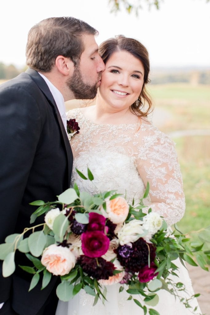 Angled view of the bride and groom, her bridal bouquet by Whisper and Brook Flower Co. prominently displayed in the photo Ballyowen Golf Course in background