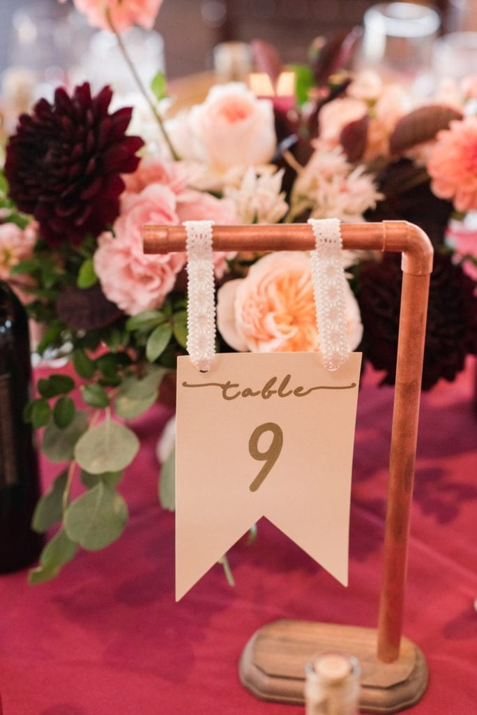 Unique table number hanging from copper piping in front of low floral arrangement of blush, cream and dark red mixed florals by Whisper & Brook Flower Co.