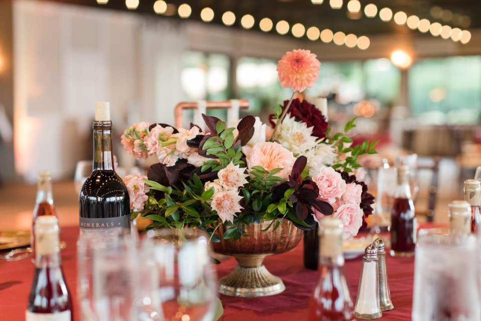 Low floral arrangement of blush, cream and dark red mixed florals by Whisper & Brook Flower Co.