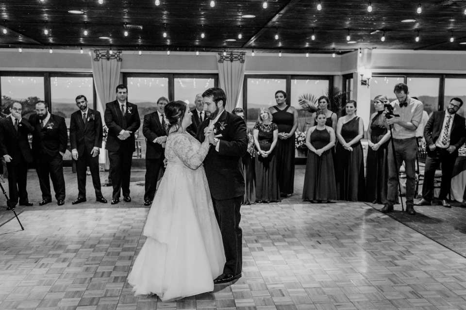 Black and white candid photo capturing the first dance, with the bridal party looking on in the background