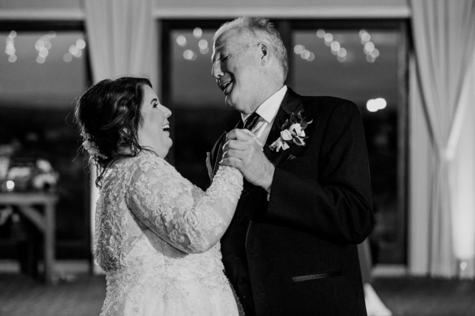 Black and white candid photo of the bride sharing a dance with her father