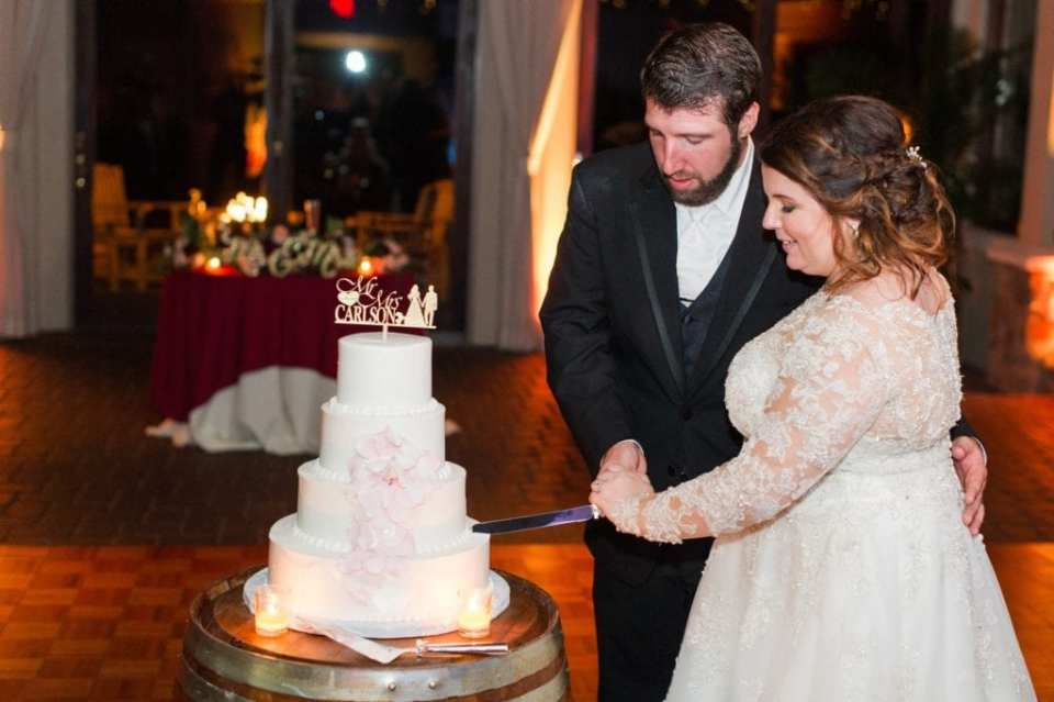 Bride and groom cutting their 4 tier white wedding cake with blush floral accents by Cafe Pierrot and custom gold cake topper