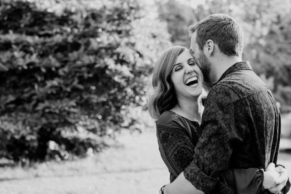 Black and white candid shot of engaged couple goofing around