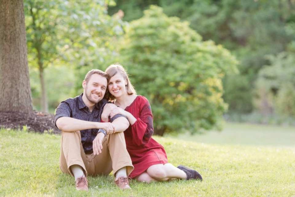 Semi-formal engagement portrait of the couple sitting in the grass, she is leaning up against him