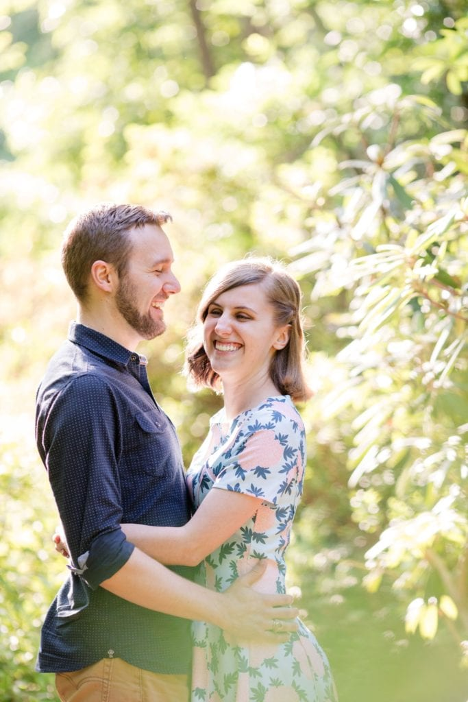 3/4 length portrait of couple laughing while embracing