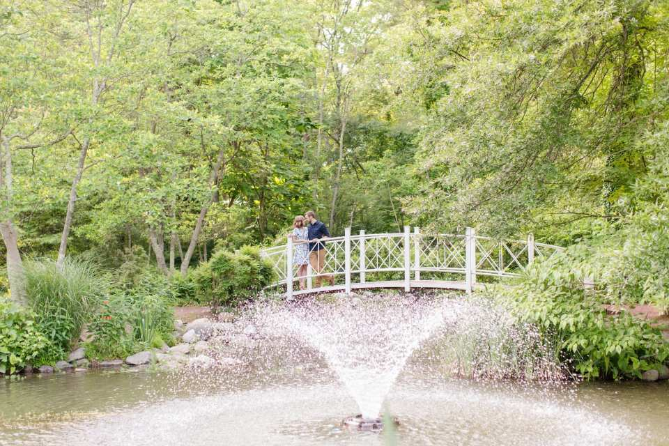 Couple on bridge behind flowing fountain, nose to nose in the Sayen Gardens