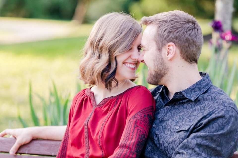 Close up photo of engaged couple sitting together, smiling while touching noses