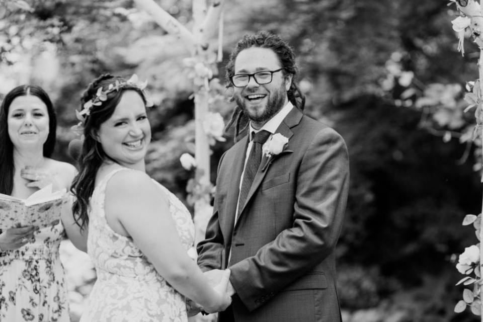 Black and white candid of the bride and groom laughing during their wedding ceremony
