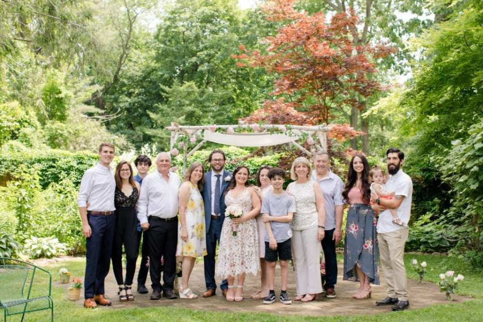 A wide angle photo of the bride and groom, their families and friends, in a group photo outside in front of the white birch chuppah during their New Jersey Micro wedding
