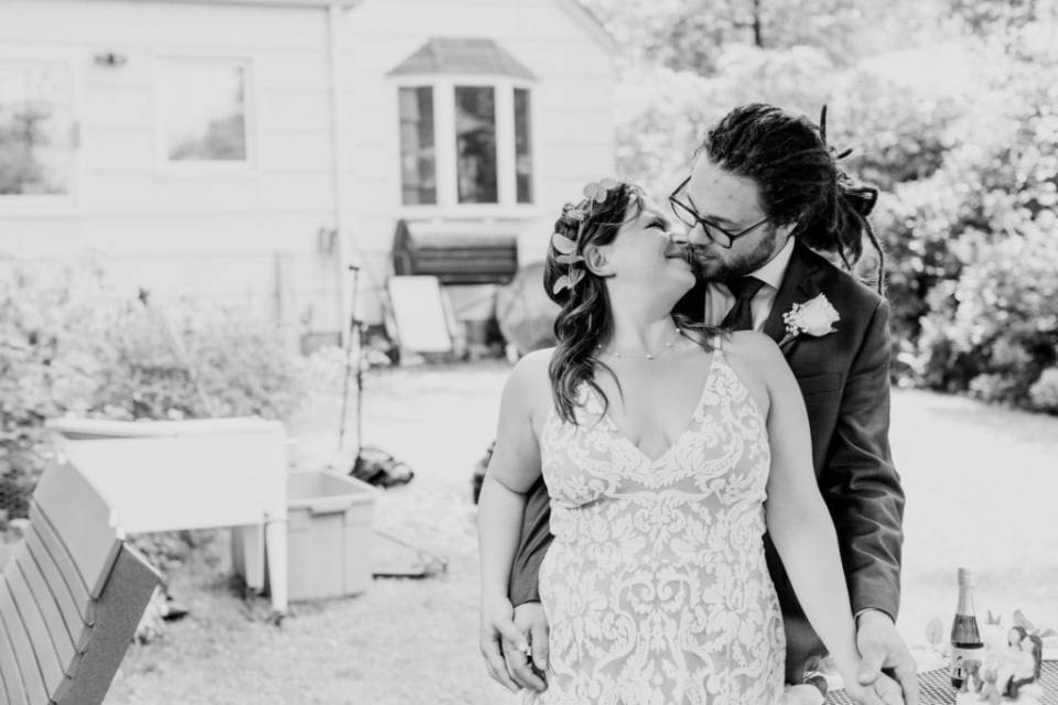 Black and white photo of the bride in her Dress the Population lace print gown sharing a intimate moment with her groom