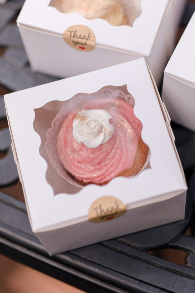 Small white windowed boxes containing custom pink frosted cupcakes for guests