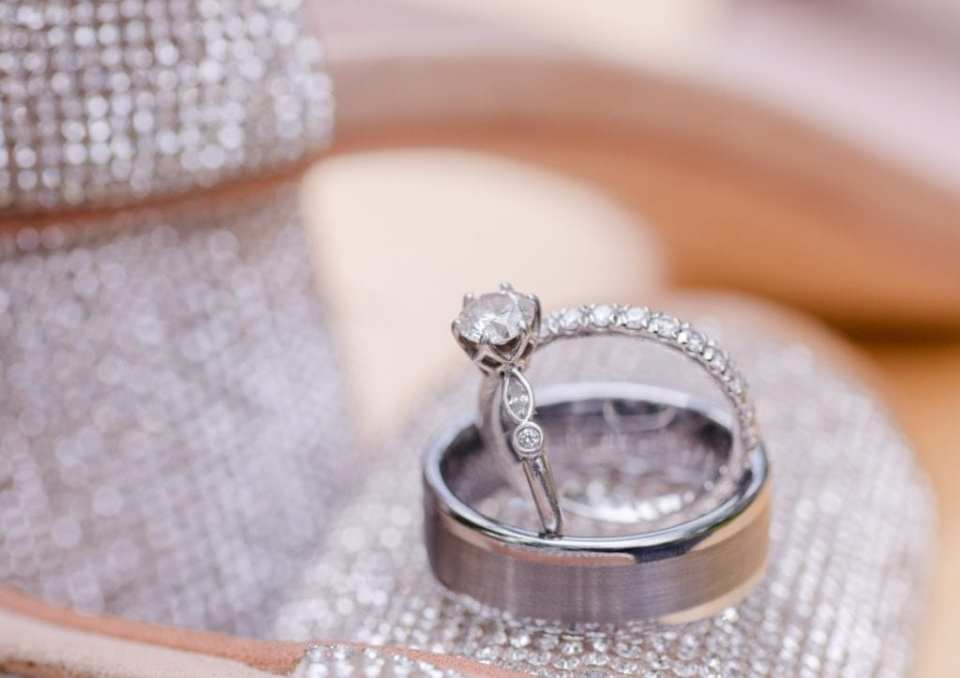 The brides round diamond engagement ring set in an antique diamond band, diamond infinity wedding band and groom's brushed platinum wedding band displayed on the heel of the brides rhinestone shoe