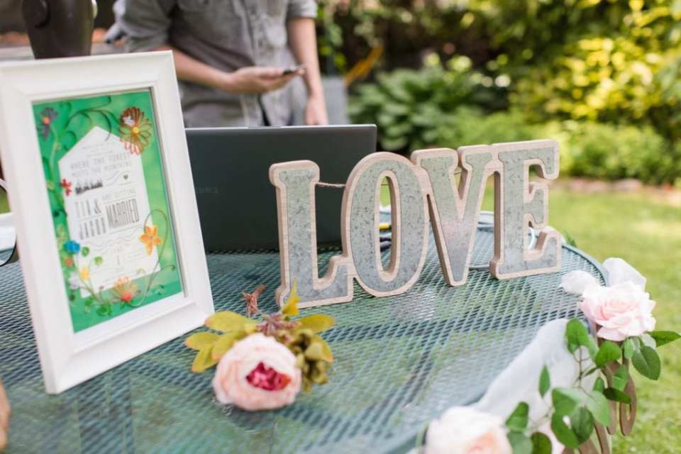 Close up of an outdoor table at the wedding, adorned with custom signage with the bride and grooms details, a LOVE sign, and a computer, part of the way the bride and groom shared their ceremony with friends and family who could not be at their wedding because of COVID-19