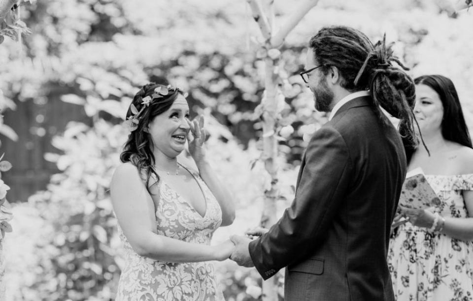 Black and white candid of the bride, wiping away tears, and groom during their wedding ceremony