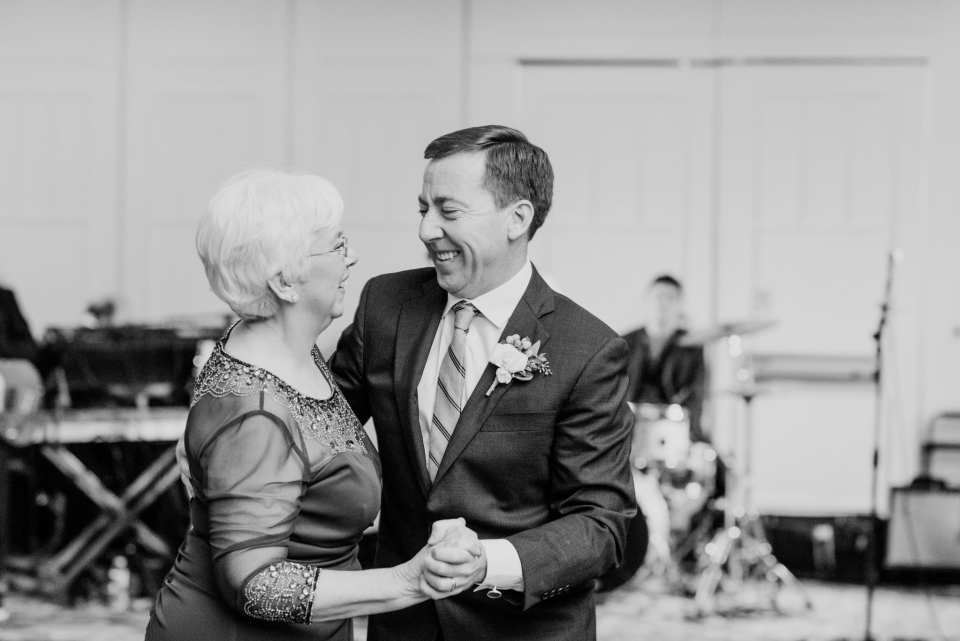 Black and white candid photo of the groom dancing with his mother