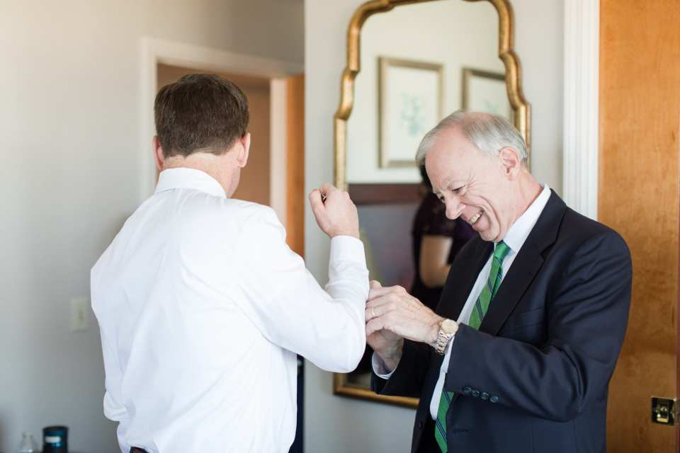 Candid of the groom being helped with his cufflinks by his father