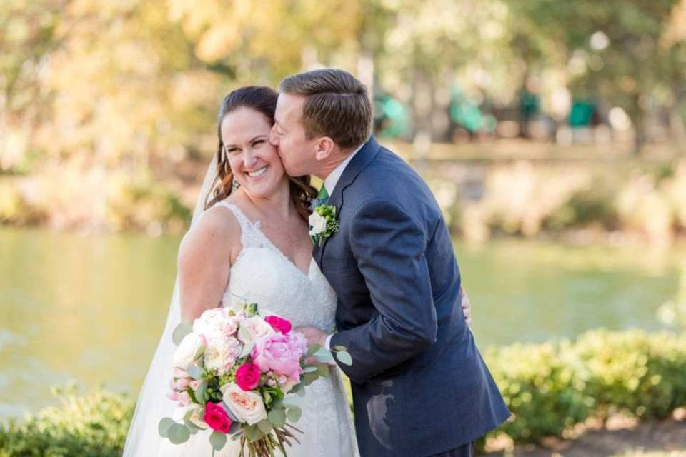 Groom kissing his smiling bride, her bouquet of pink florals by Wallflowers on full display