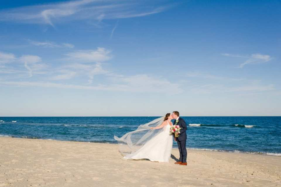 Wide angle photo of the bride and groom kissing on Spring Lake beach, waves in the background, her veil flowing in the wind behind her