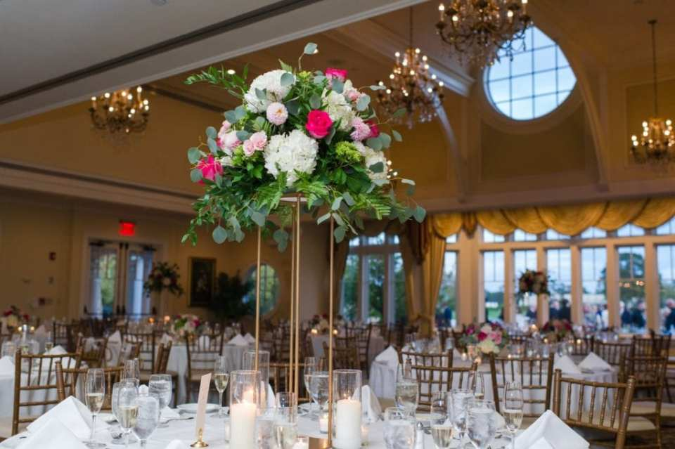 Photo of tall florals on reception tables consisting of a variety of hydrangeas, roses and assorted pink flowers by Wallflowers