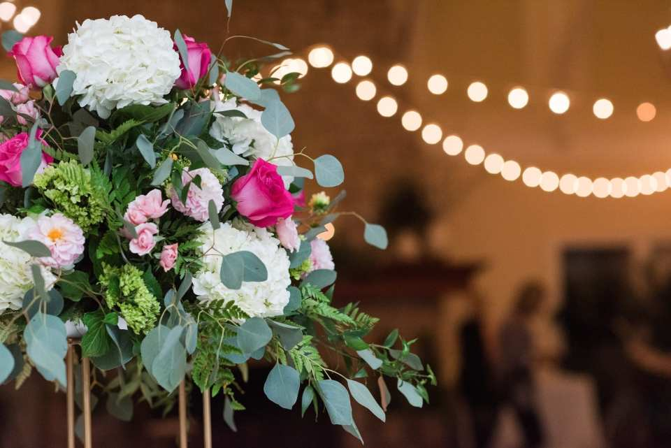 Close up shot of tall florals on reception tables consisting of a variety of hydrangeas, roses and assorted pink flowers by Wallflowers in this Spring Lake Golf Club wedding