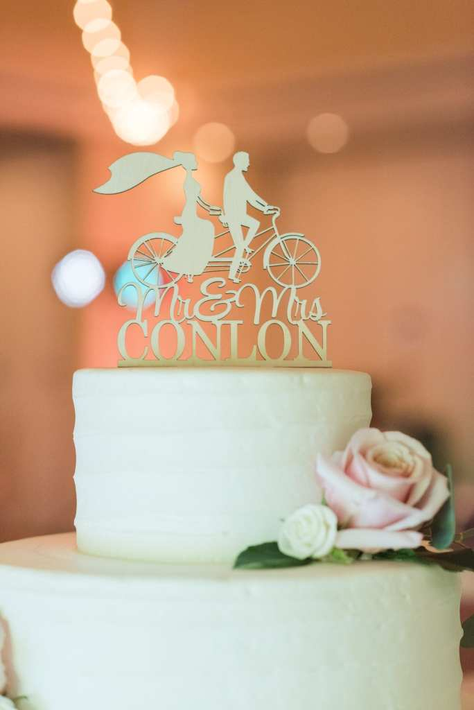 The top layer of the light green wedding cake with a custom topper at this Spring Lake Golf Club wedding
