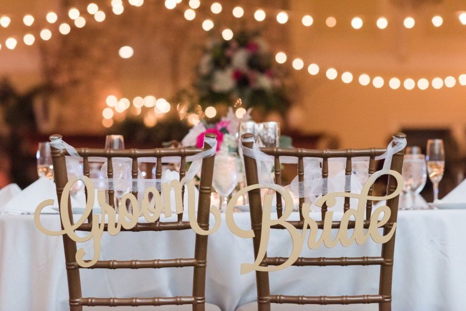 Wedding detail shot: the back of the bride and groom's chivari chairs personalized with signage in the reception ballroom of their Spring Lake Golf Club wedding