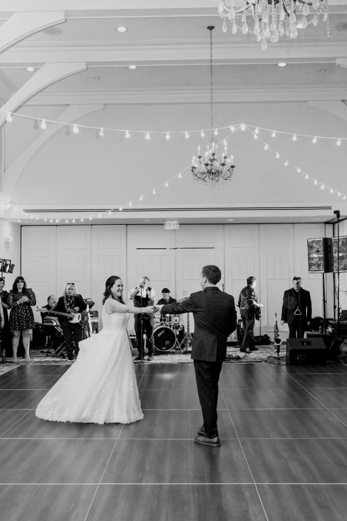 Black and white photo of the bride and groom during their first dance in the ballroom of their Spring Lake Golf Club wedding