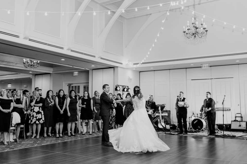 Black and white wide angle photo of the bride and groom during their first dance at their Spring Lake Golf Club wedding