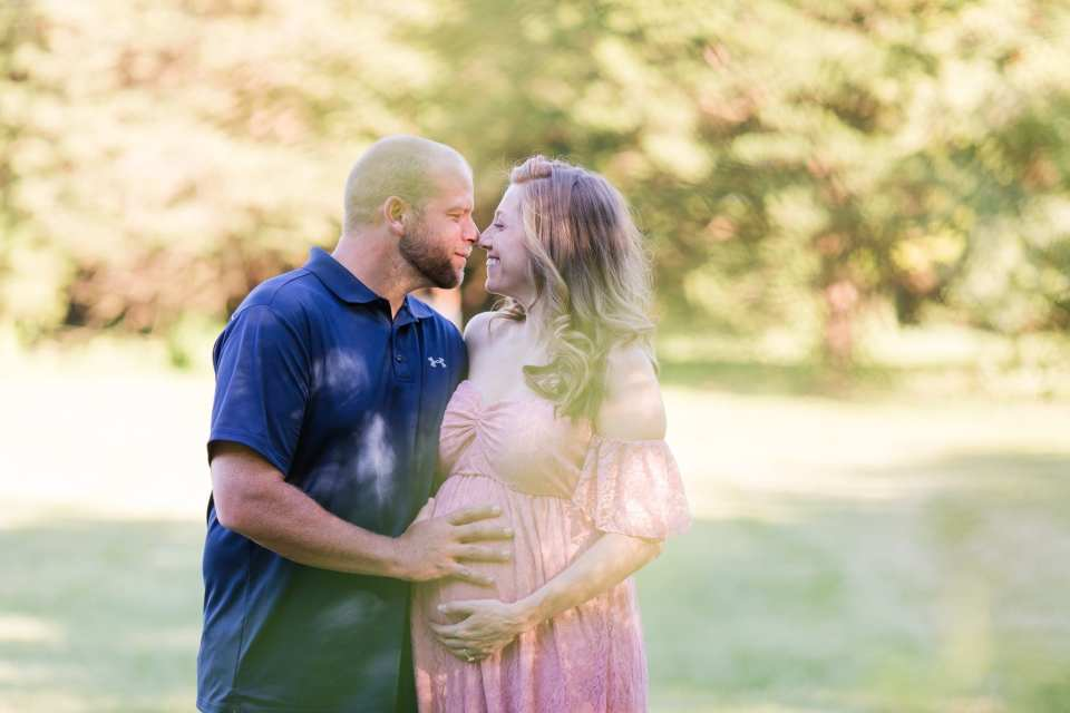 Sunlit photo of the parents to be smiling, nuzzling their noses in these New Jersey maternity photos