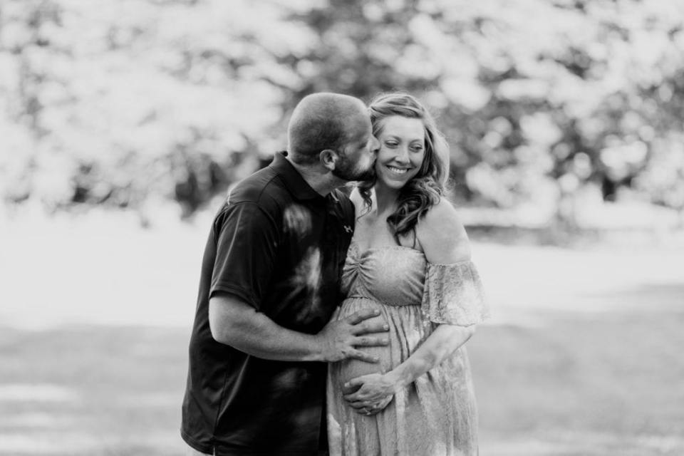 Black and white candid photo of the parents to be; Mom to be smiling looking away as her husband kisses her cheek and places his hand on her pregnant belly