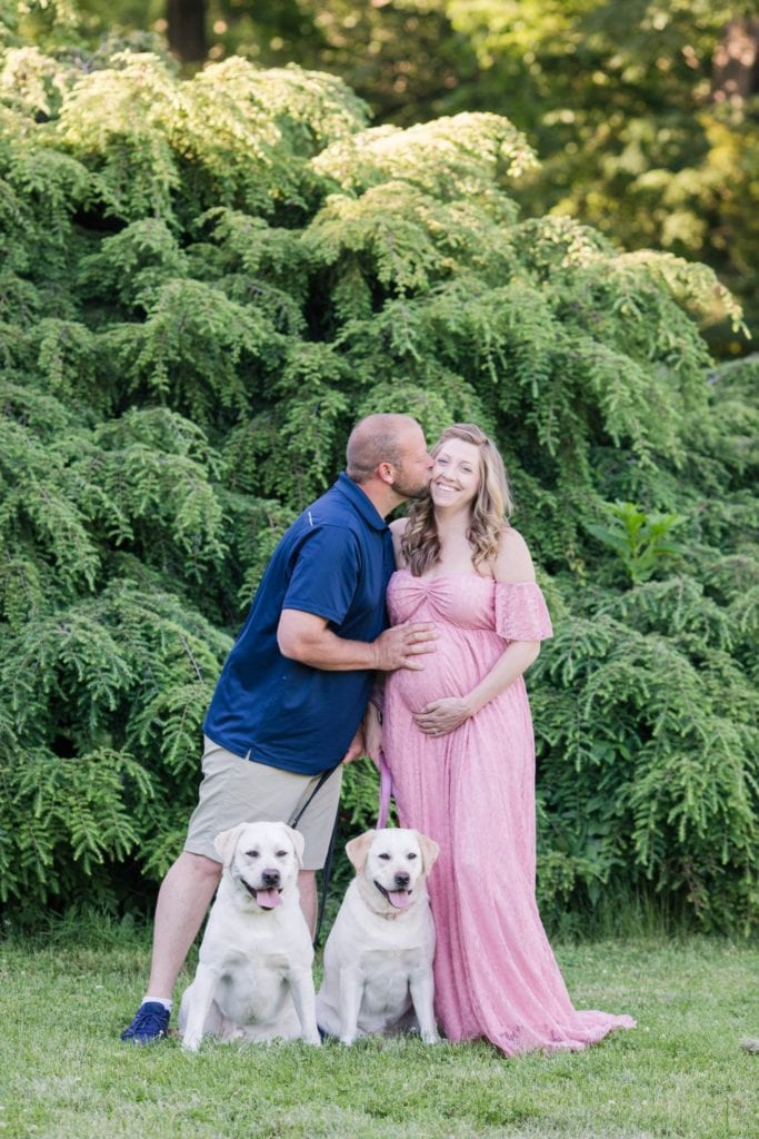 Mom to be in long pink off the shoulder maternity gown being kissed on the cheek by her husband as they are standing, holding their two dogs leashes, both dogs sitting in these New Jersey maternity photos