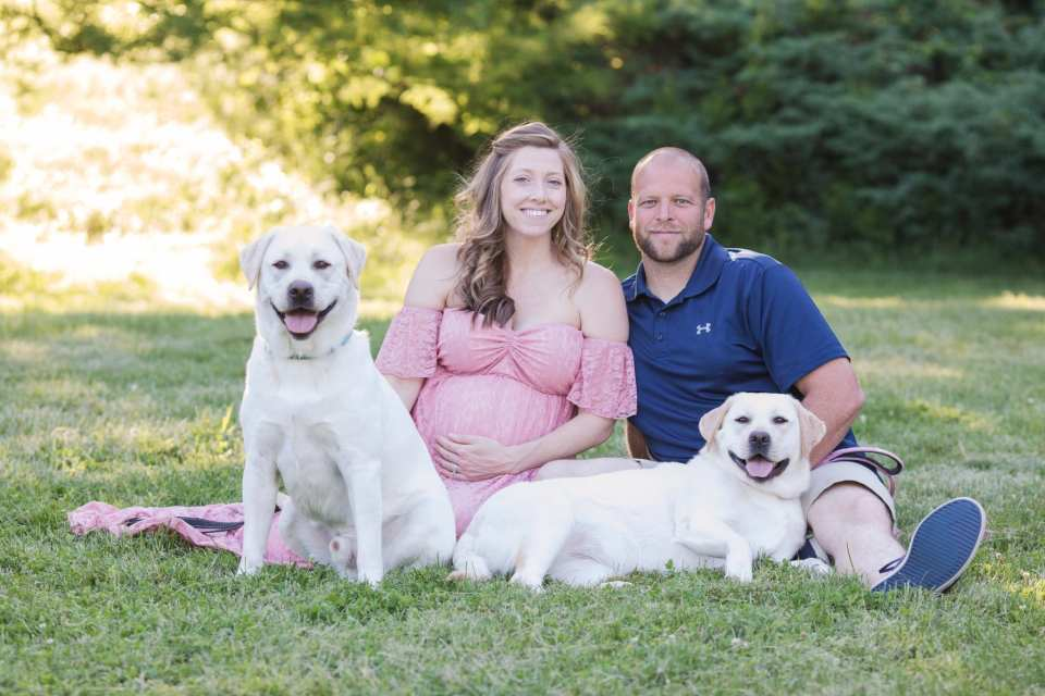 Pregnant Mom and Dad smiling while sitting on the grass amongst the foliage at Rutgers Gardens, their two lab pups laying down right along with them