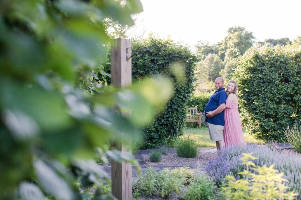 """Mother to be standing behind her husband, the father to be, with her arms wrapped around his """"pregnant"""" belly. She is smiling. The photo is being taken from behind foliage across the garden"""