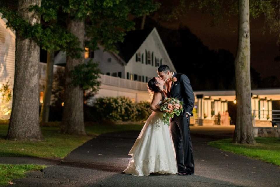 The bride and her groom kiss outside at night in front of the main building in these Ryland Inn wedding photos