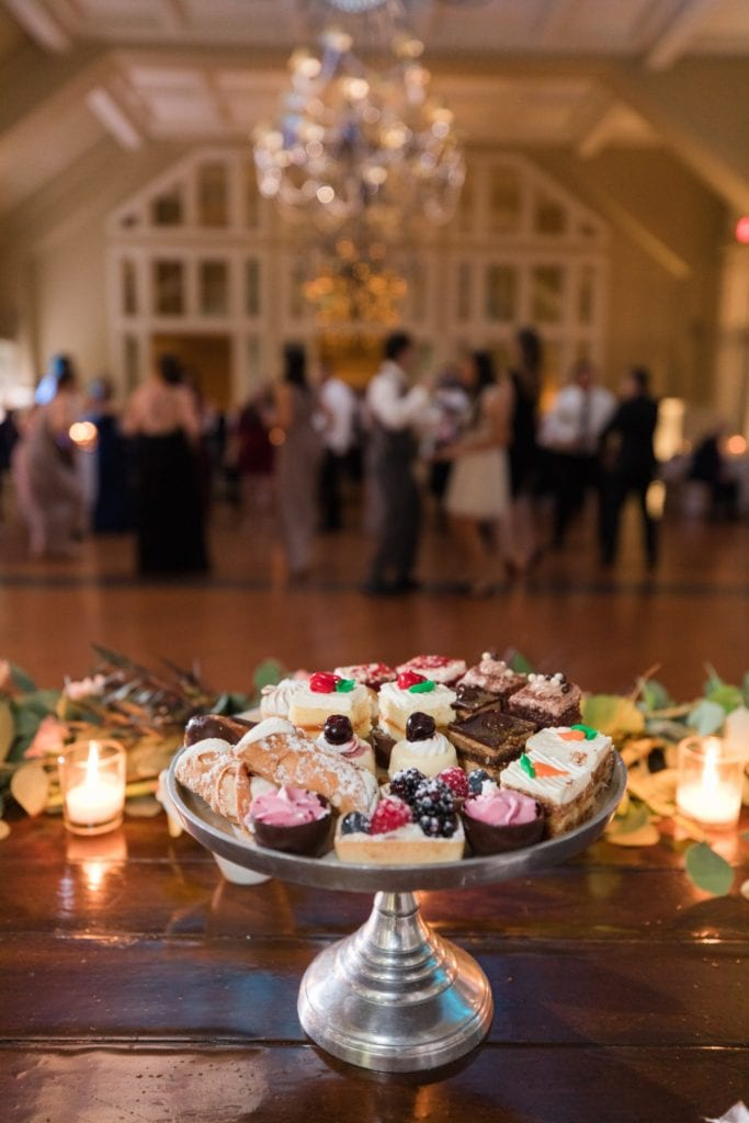 Dessert tray highlighted with guests dancing in the background at the Ryland Inn