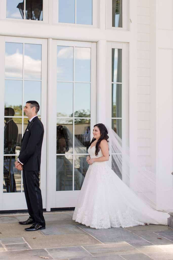 The bride coming up behind her groom during the first look outside the Ryland Inn