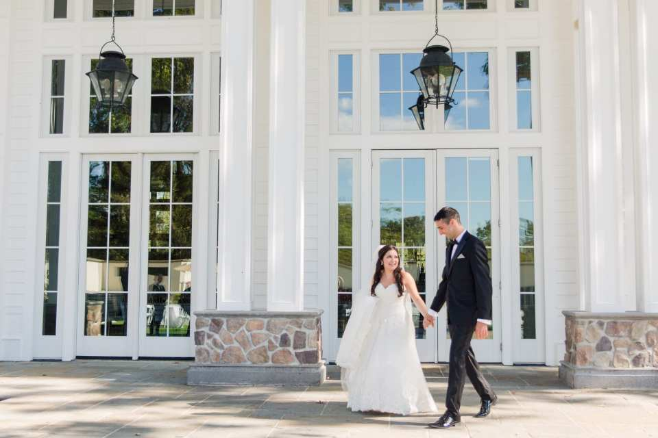 The bride and groom take a stroll during their first look outside the Ryland Inn
