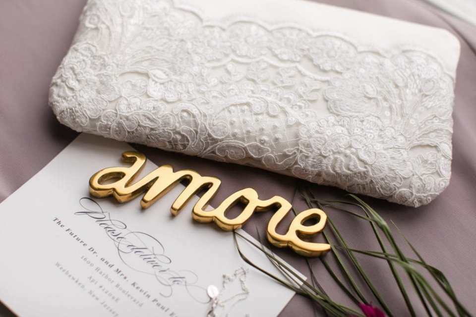 Close up of wedding invitation suite by Minted on display with wedding jewelry and florals and custom made purse
